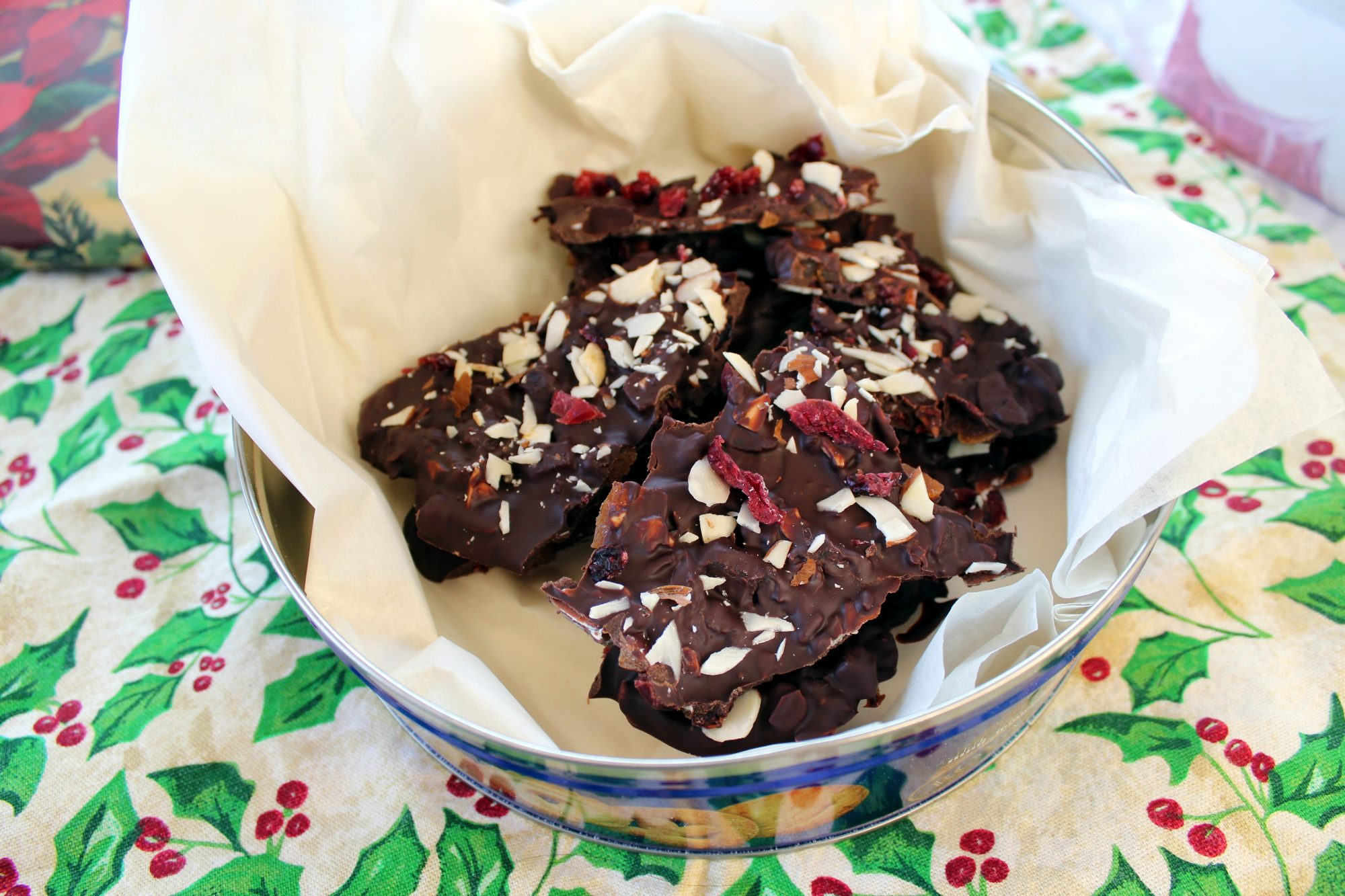 chocolate bark candy with almonds, dried cranberries, and dried apricots in a gift tin