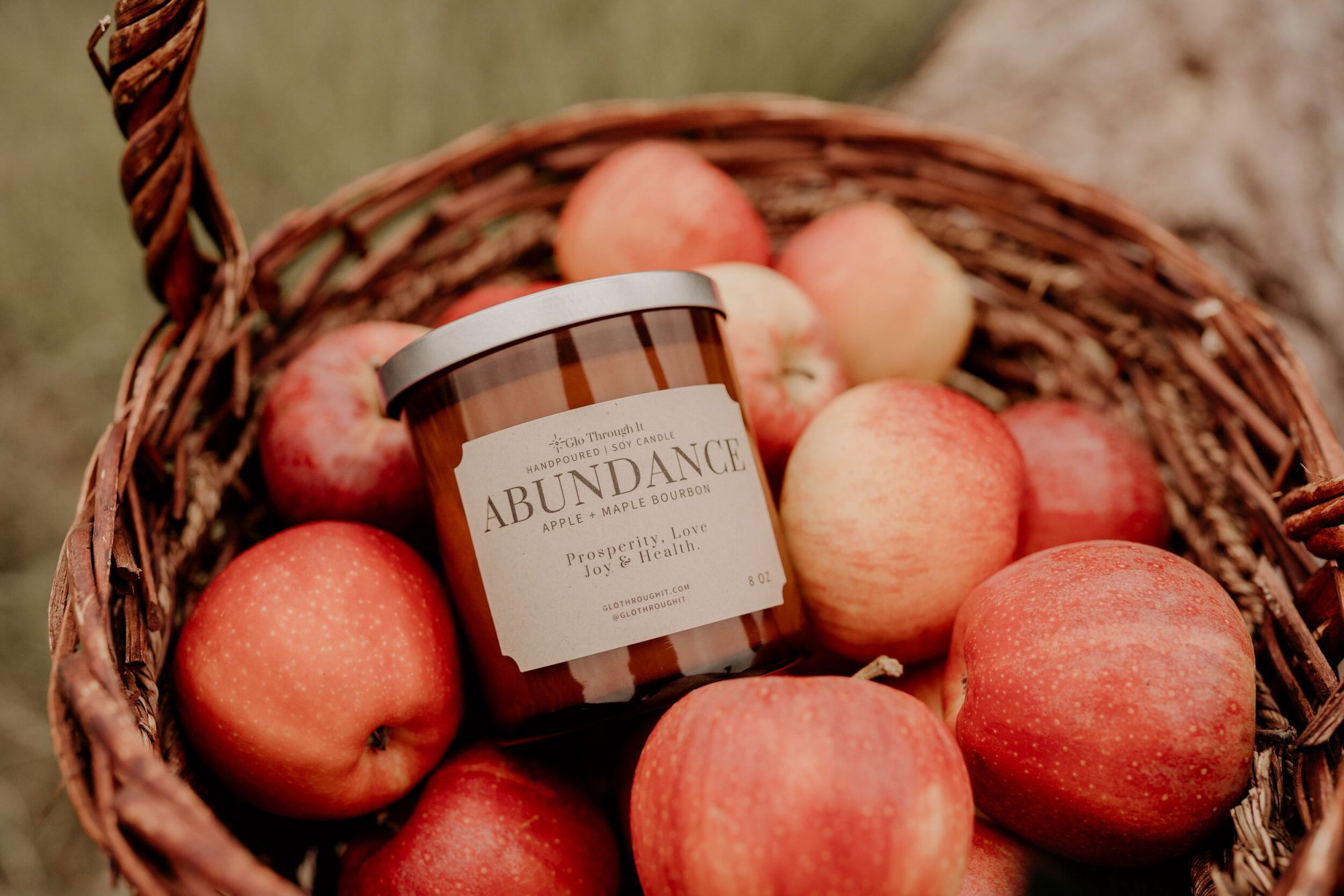 Abundance amber candle in basket of apples