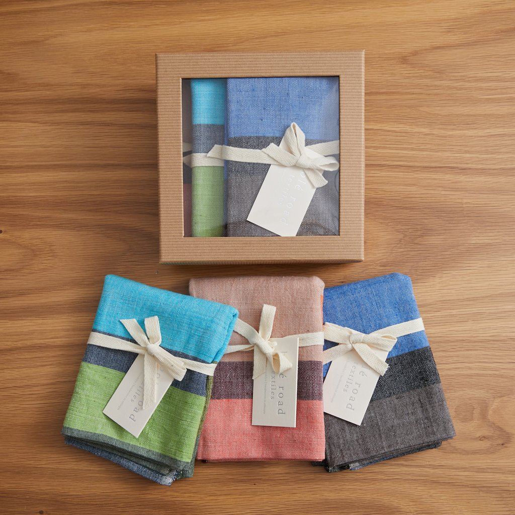 Set of three striped tea towels next to cardboard package