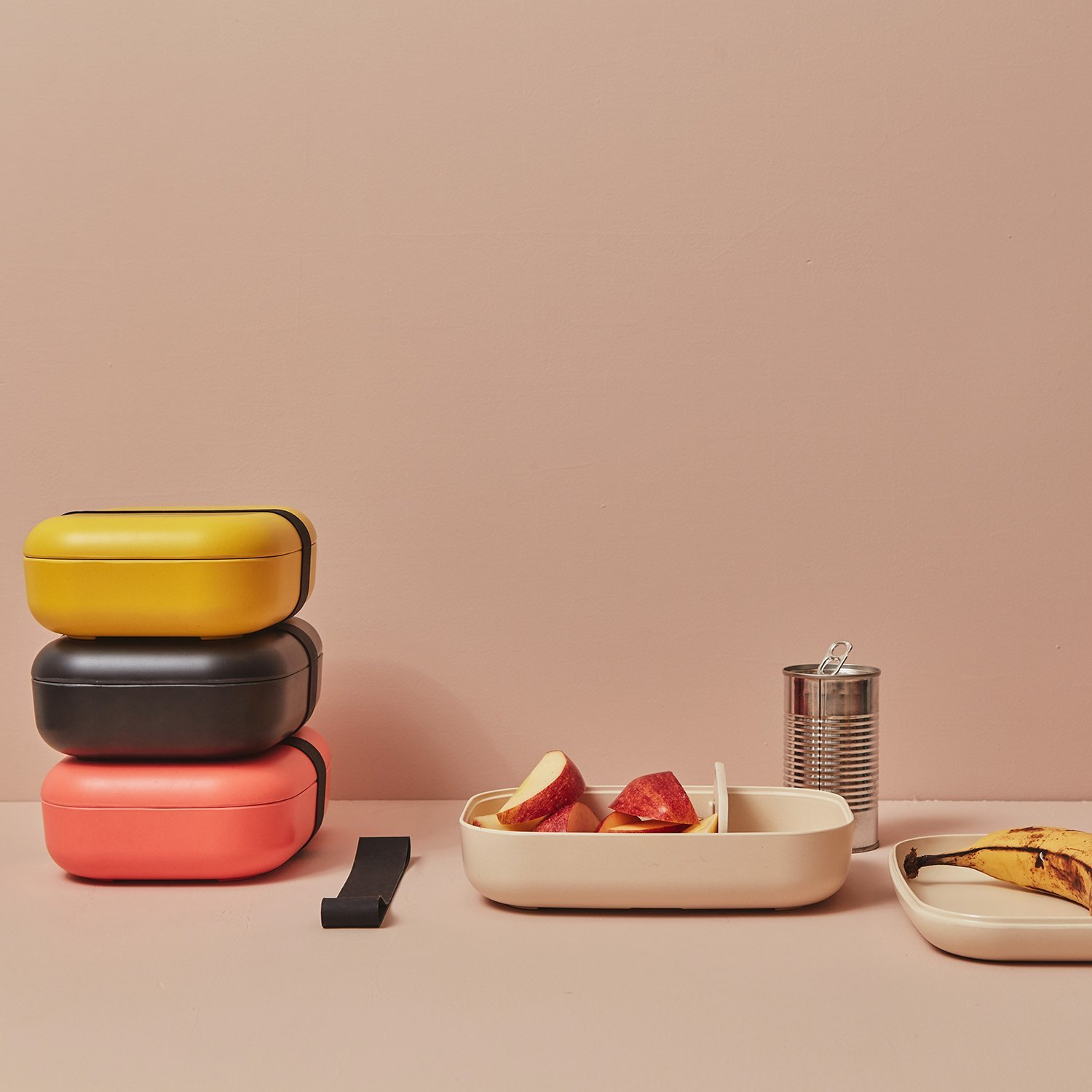 Set of four bento boxes in different colors, one with apples inside