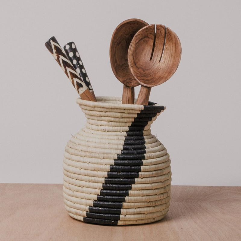 Woven utensil holder with wooden utensils inside