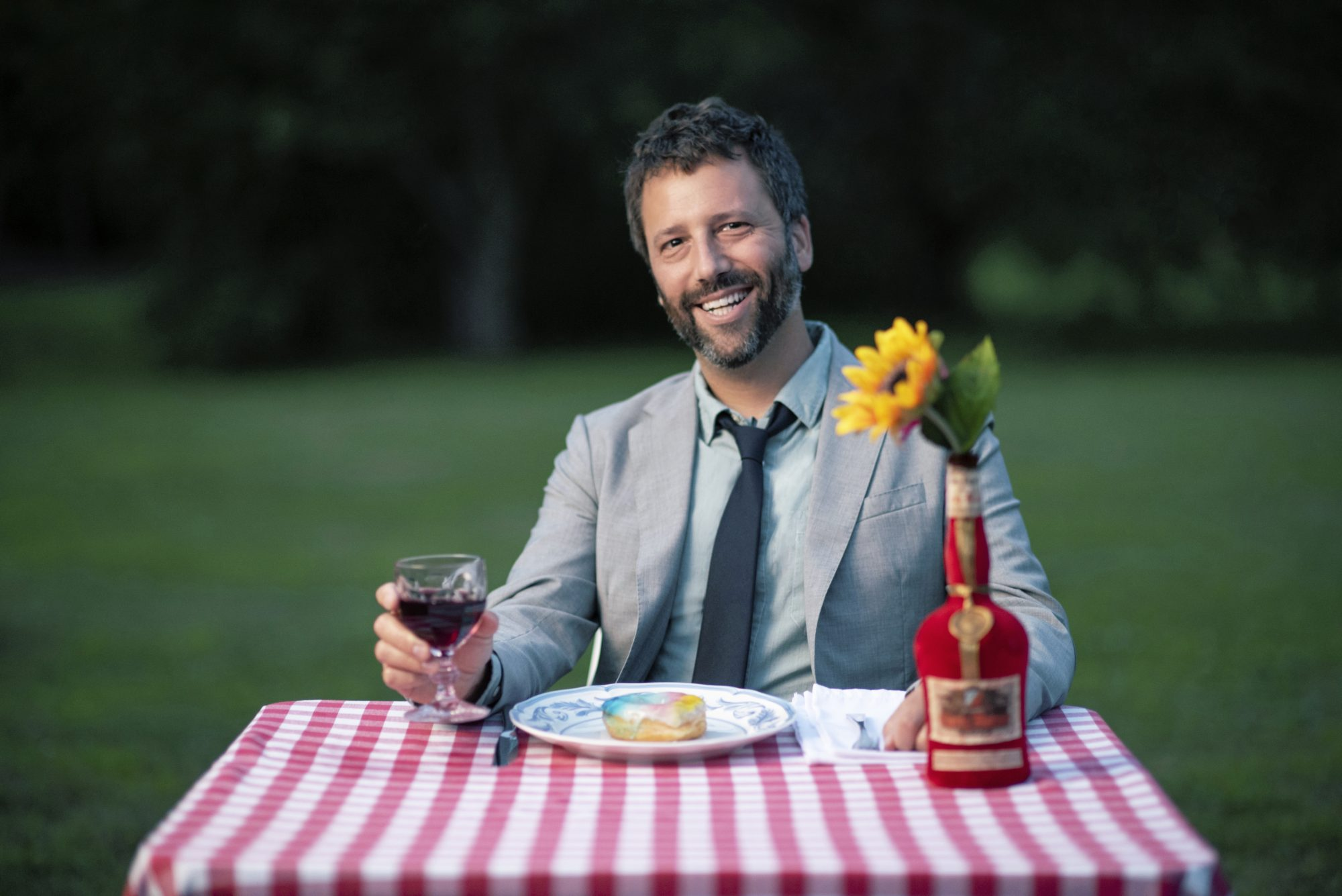 Dan Pashman sitting at a table in a field holding a glass of wine