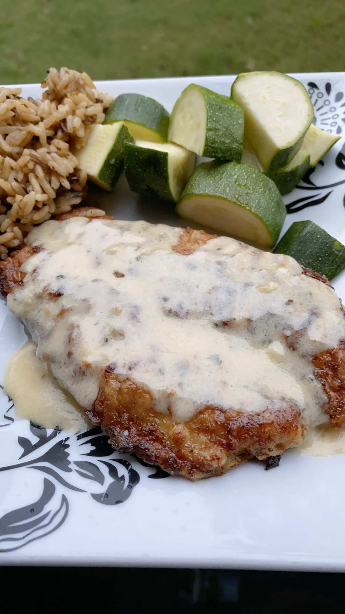 breaded chicken in lemon sauce with zucchini on the side