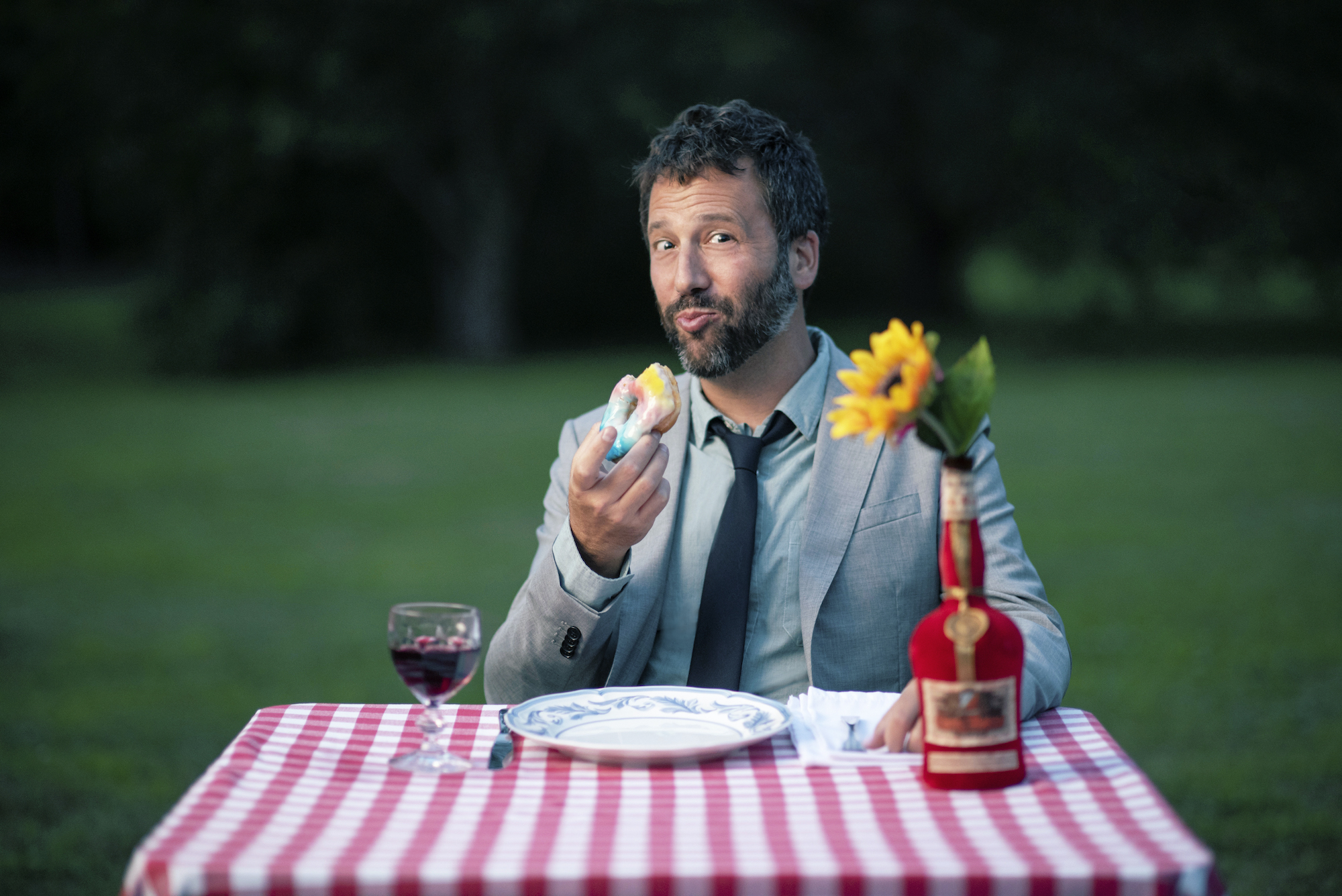 Dan Pashman eating a donut at a table in a field
