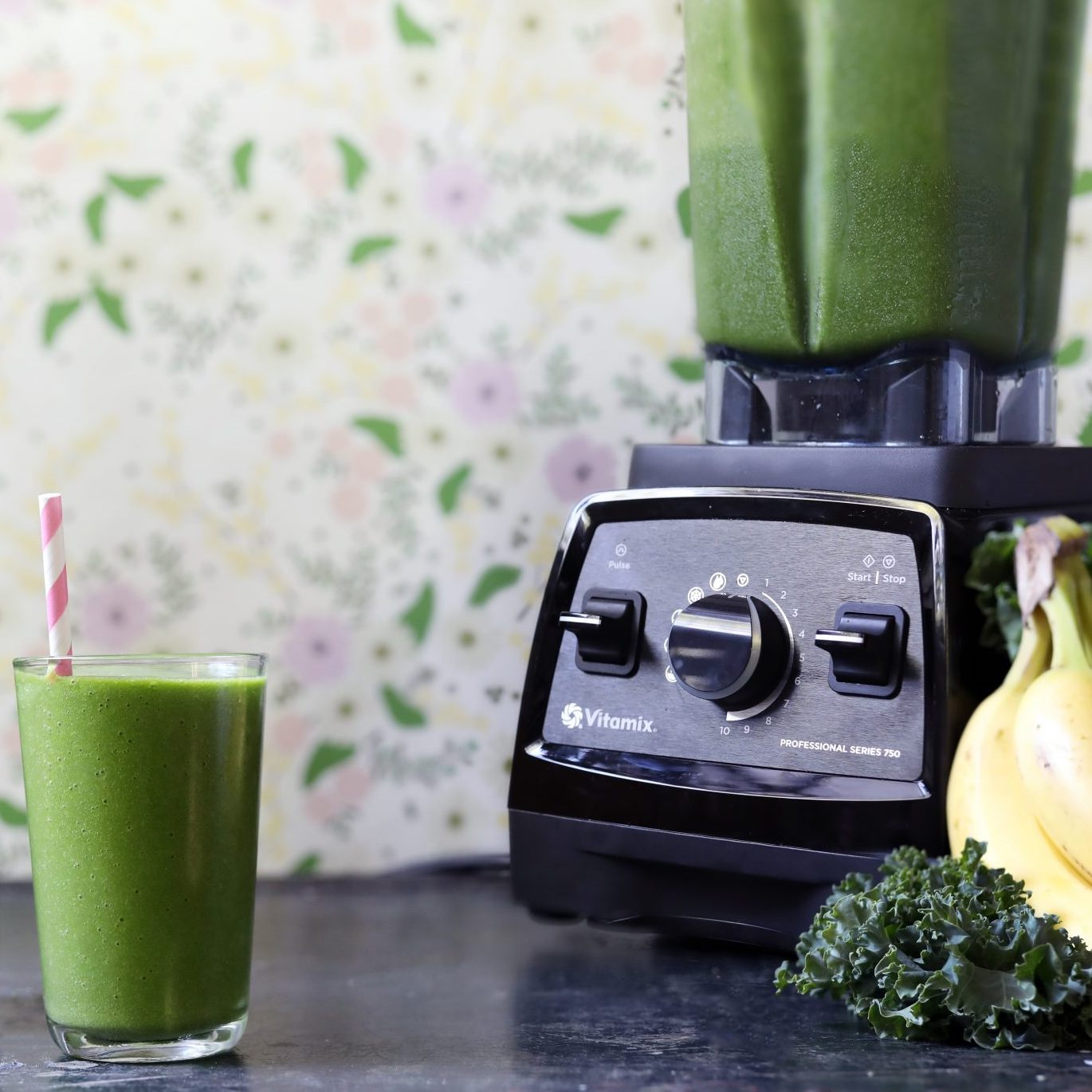 Vitamix blender with green smoothie inside pitcher, plus two cups of green smoothie, banana, kale, and pineapple