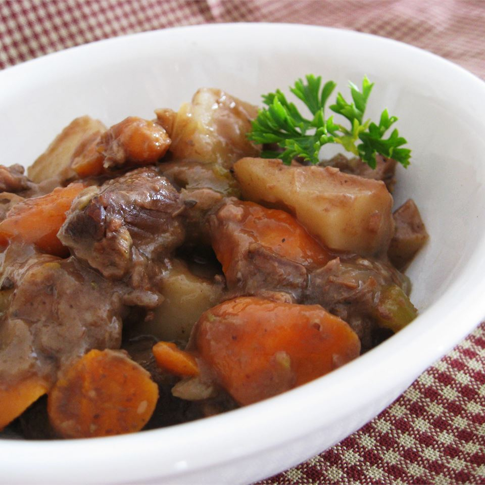 white bowl full of beef stew with carrots and potatoes