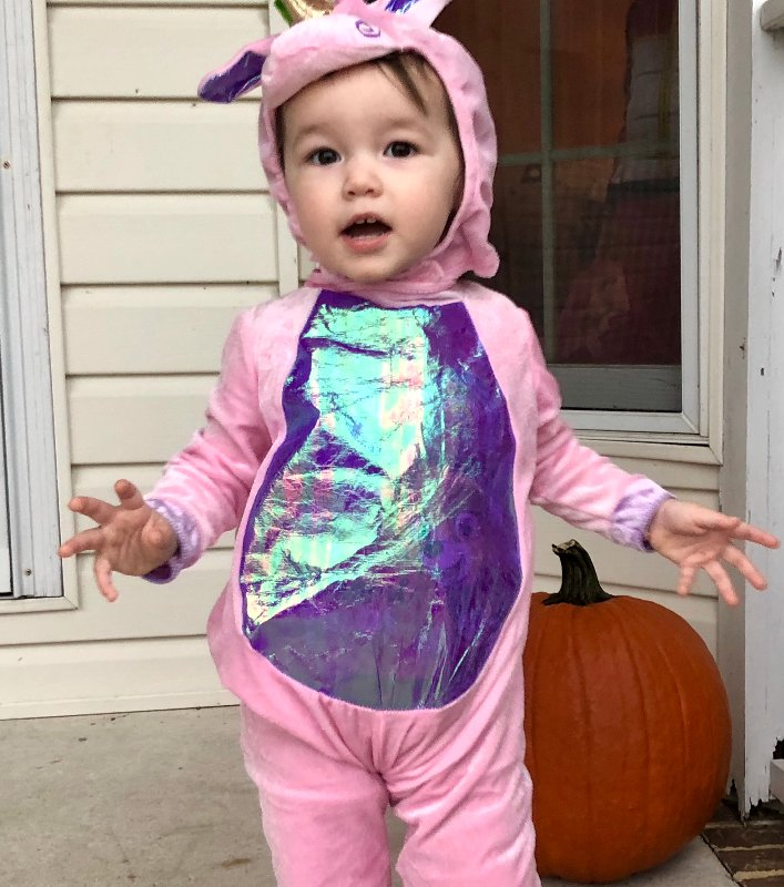 child dressed up in pink and purple unicorn Halloween costume