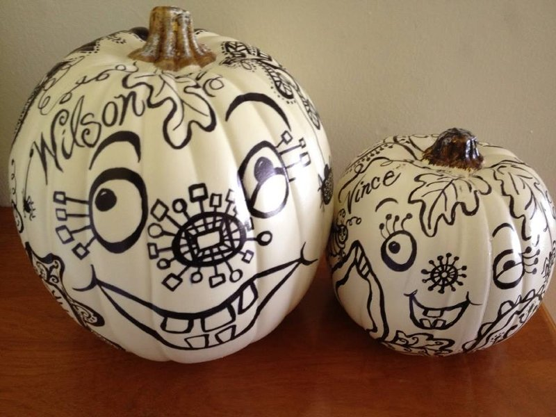 two white pumpkins with black ink designs