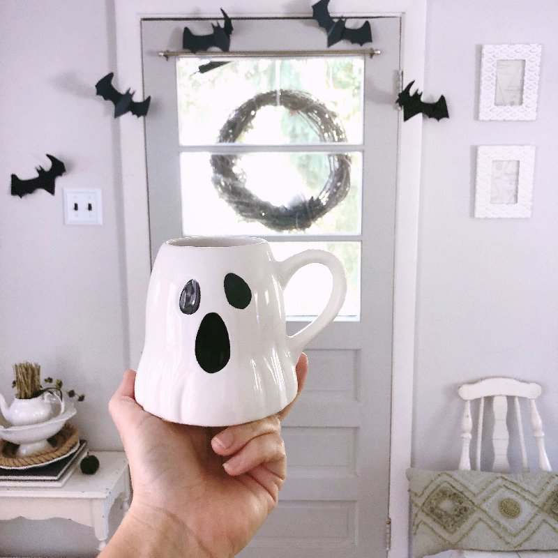 hand holding a ghost mug in front of bat Halloween decorations around the door