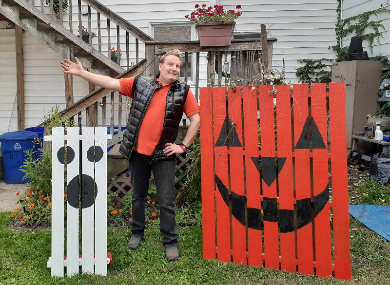 man standing with two fences painted to look like a ghost and a jack o lantern
