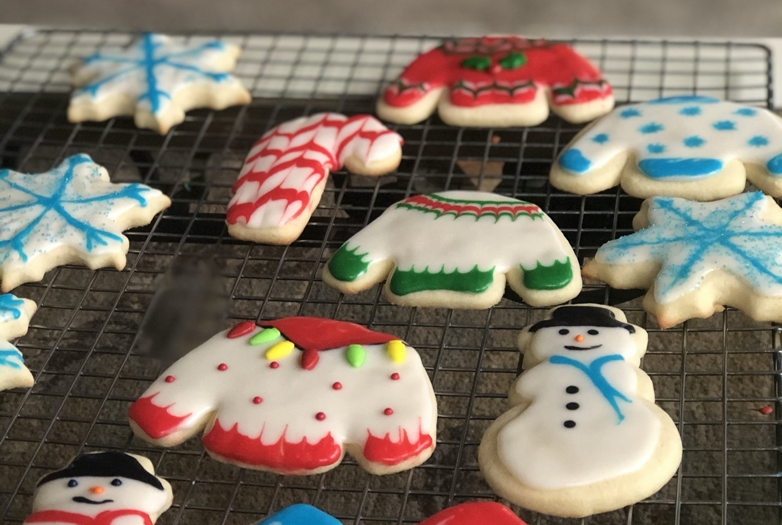 sugar cookies shaped like Christmas sweaters, snowmen, candy canes, and snowflakes