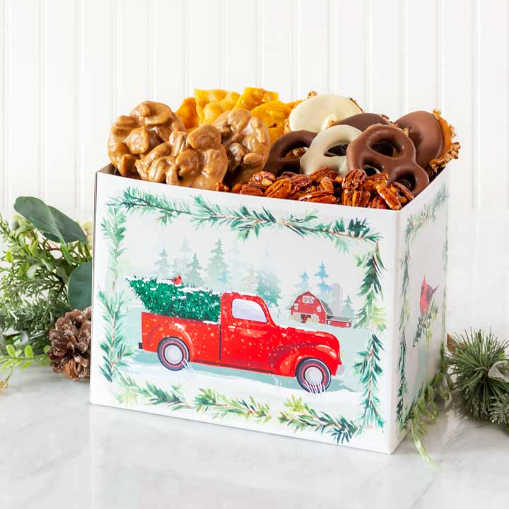 Box with red truck design and pralines, chocolate-covered pretzels, peanut brittle, and candied pecans inside