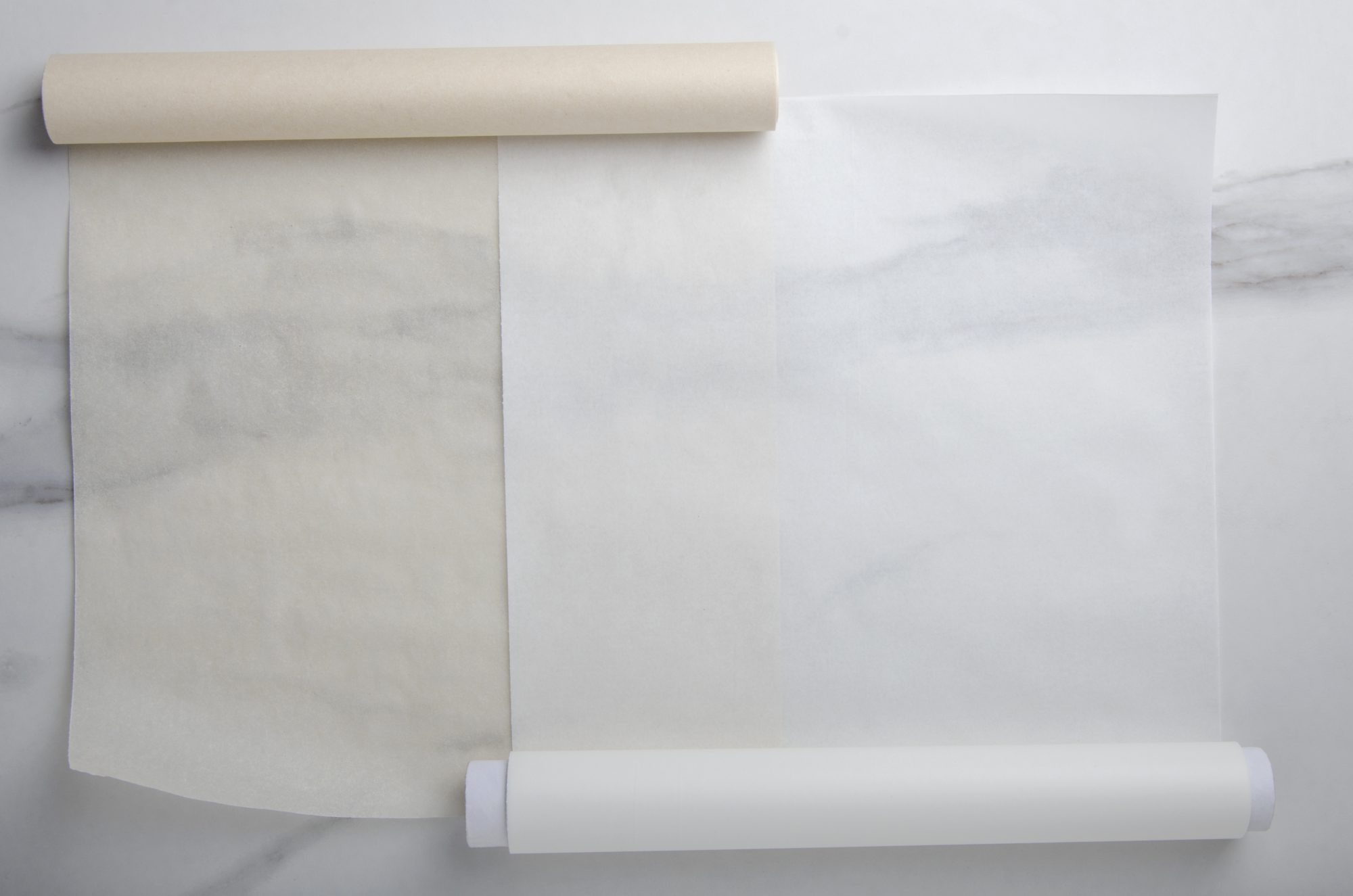 one roll of parchment paper and one roll of wax paper on a desk