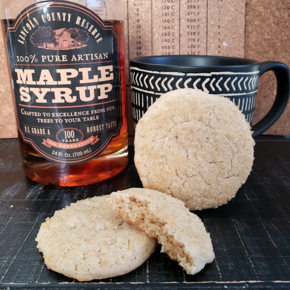 Ultimate Maple Snickerdoodles next to a bottle of maple syrup