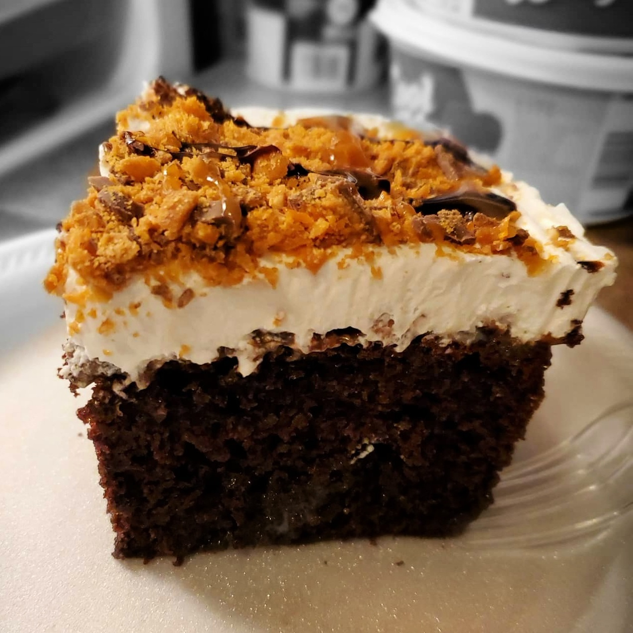 slice of chocolate butterfinger caramel cake topped with whipped cream