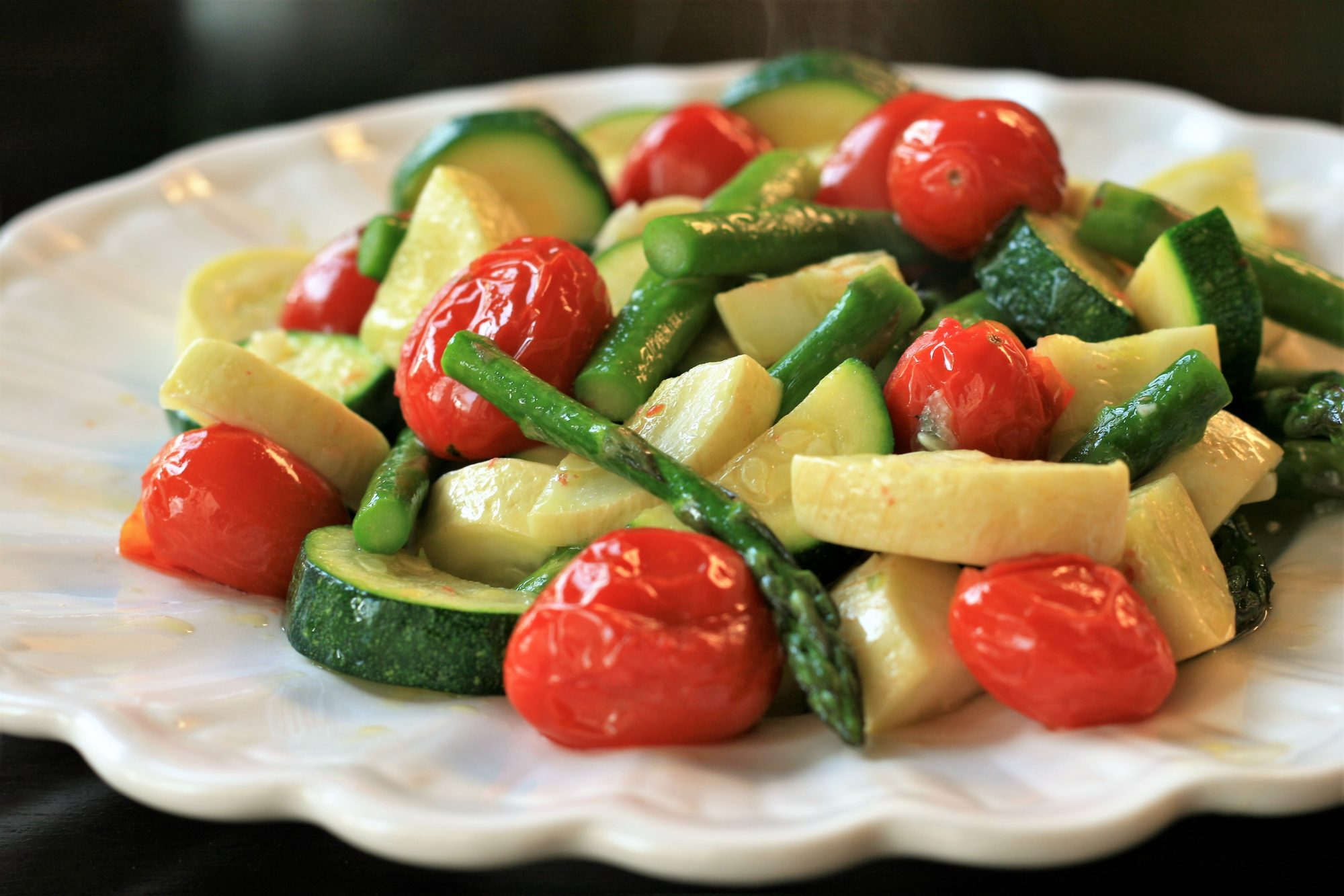 White dish with roasted asparagus, zucchini, cherry tomatoes, and squash