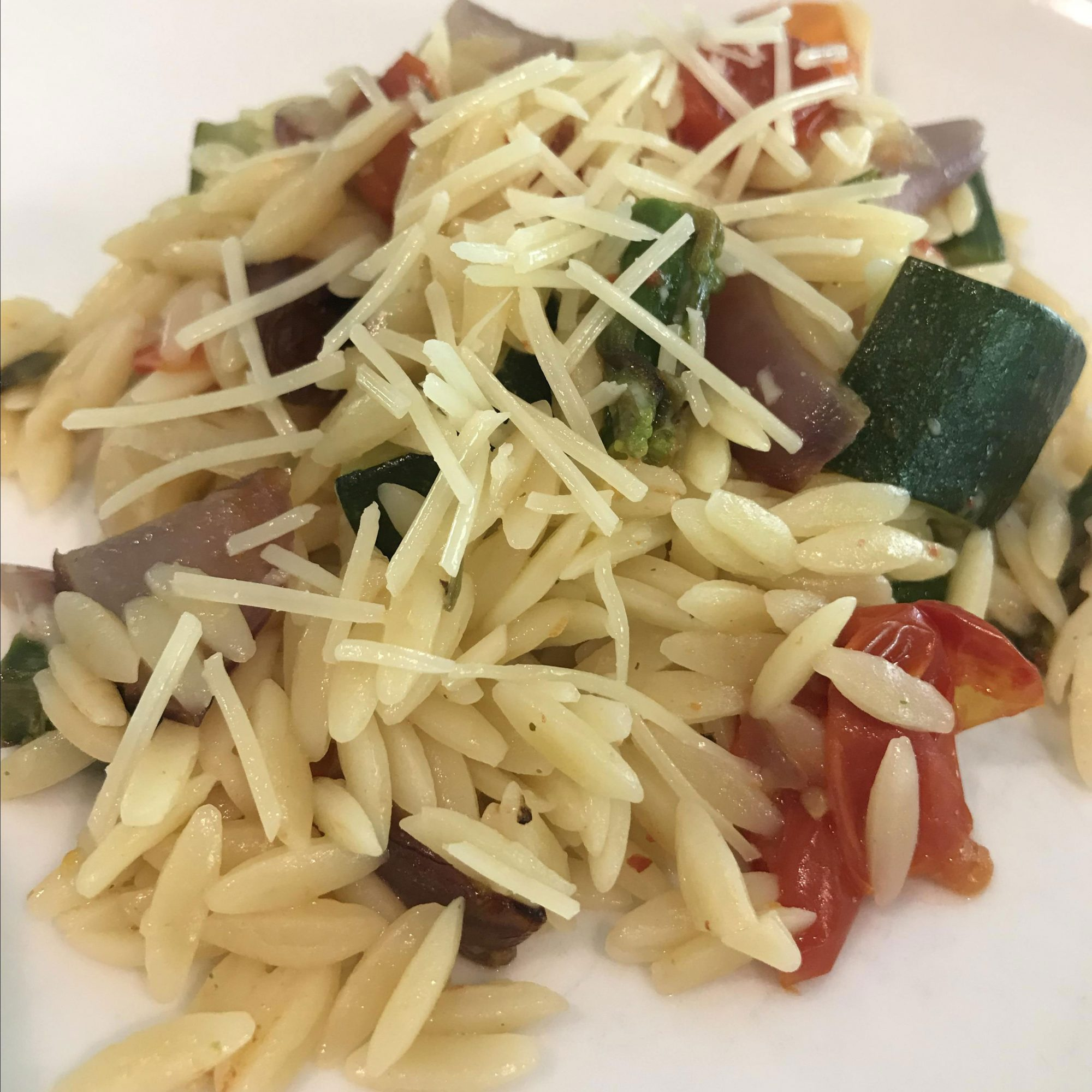 Tight shot of orzo and roasted vegetable salad with parmesan topping