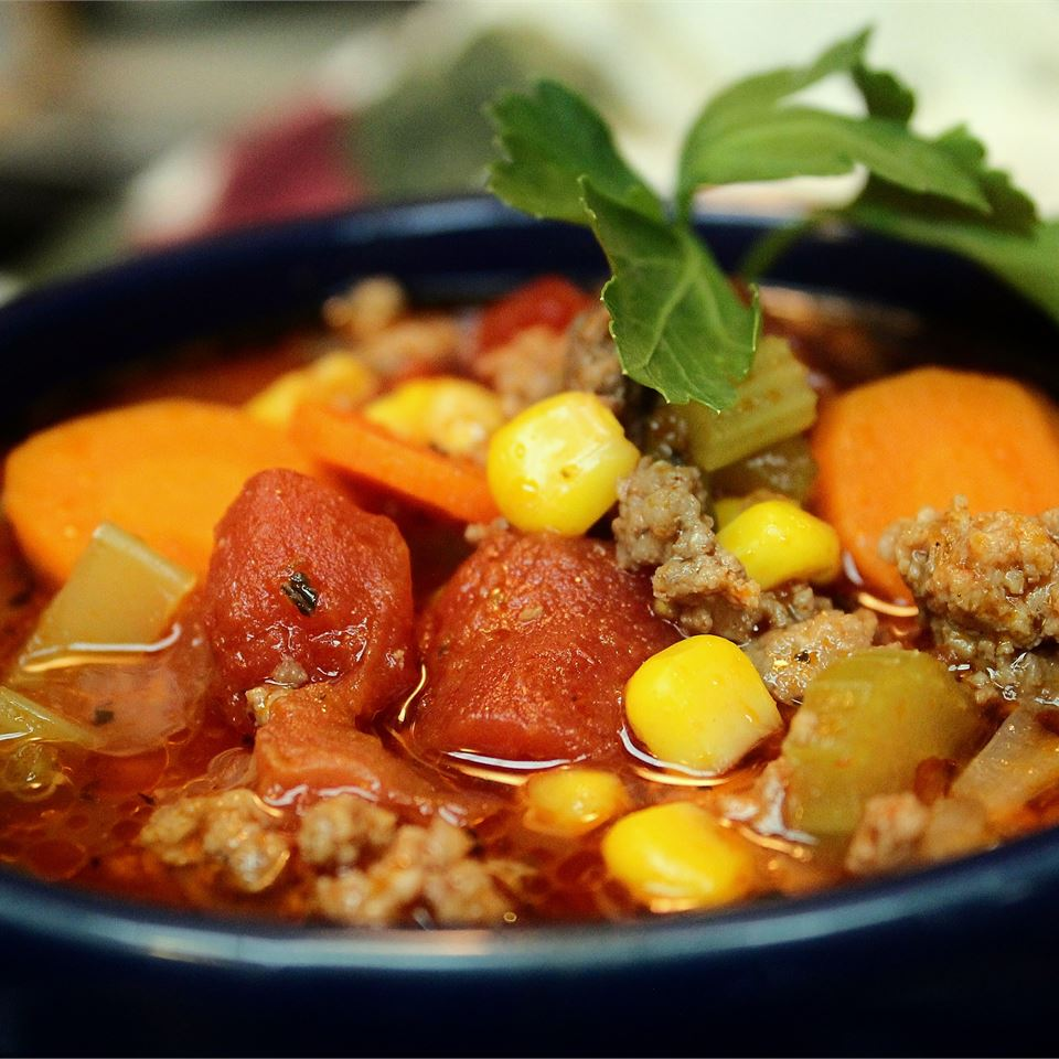 hamburger soup with corn and carrots in beans in a blue mug or bowl
