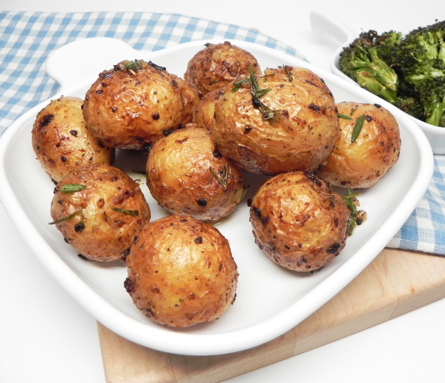 roasted baby potatoes on white serving board with a gingham towel