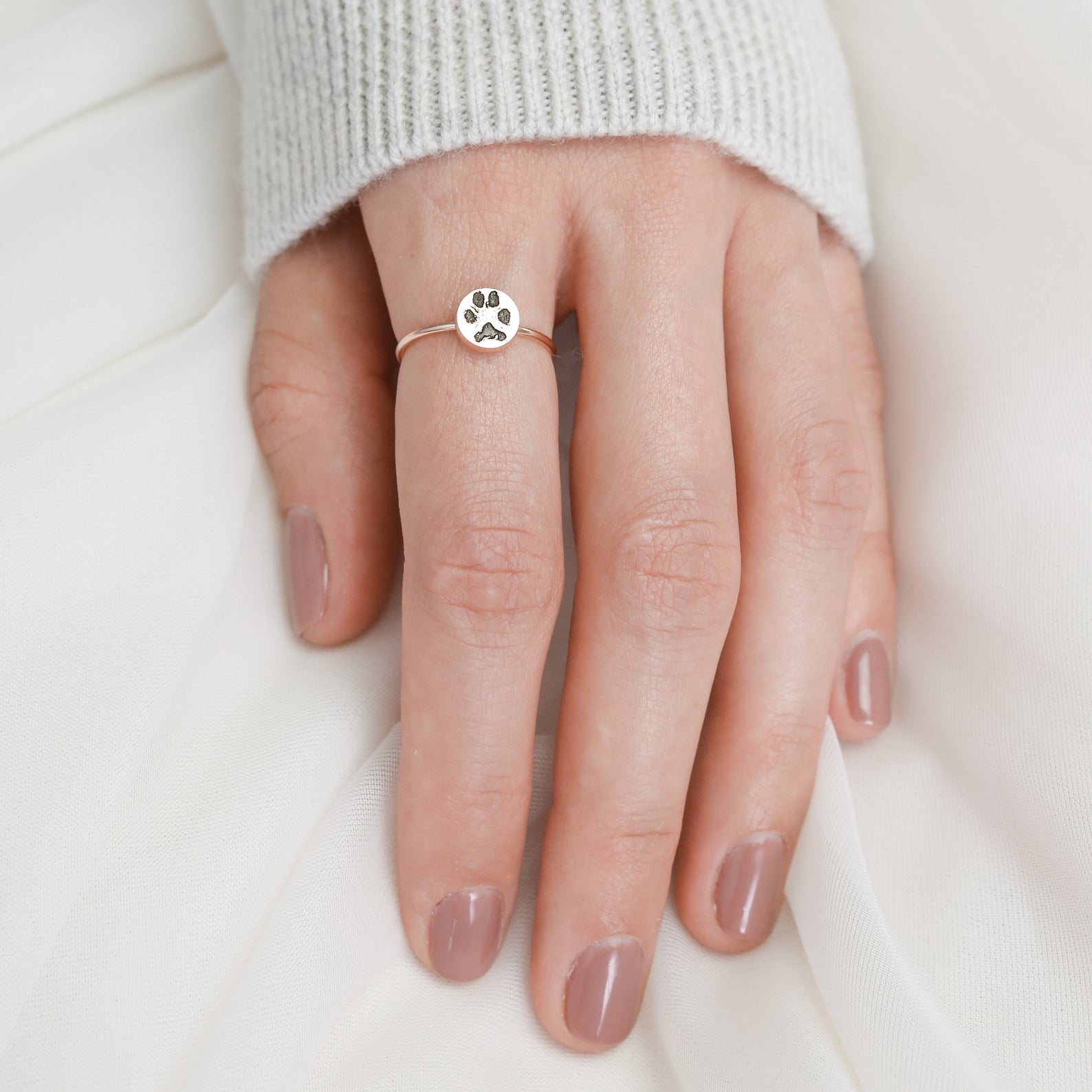 Hand with small ring with paw print stamped on it