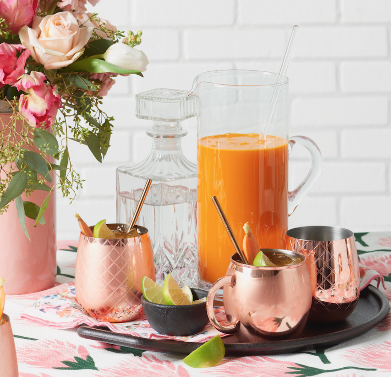 pitcher of carrot ginger mules with copper mugs