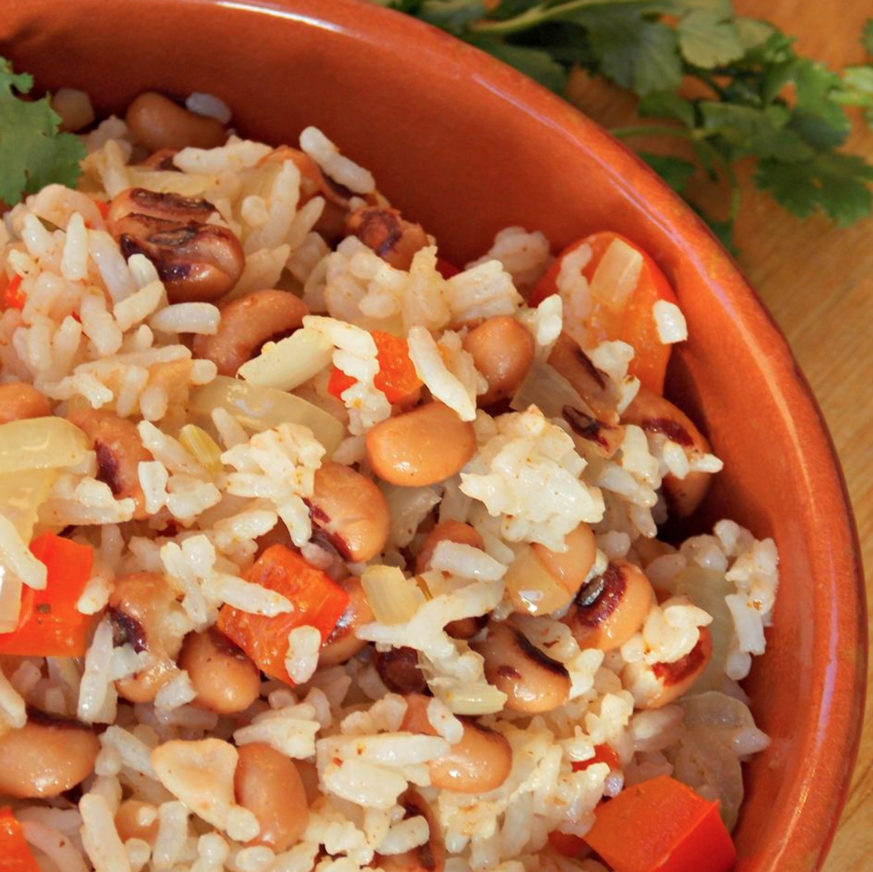 close up of hoppin john in a red bowl