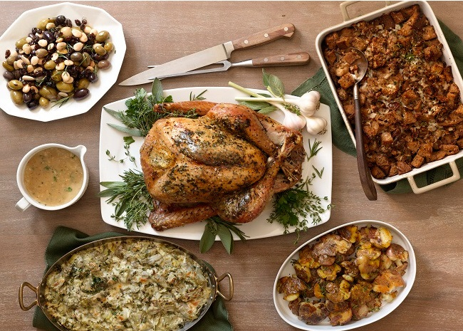 thanksgiving turkey on a platter surrounded by side dishes