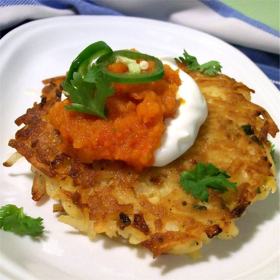 These spicy, jalapeno potato latkes are served with a homemade tomato sauce. For extra heat, do not seed jalapeno peppers. A cooling Mexican crema will go perfectly with these pancakes.