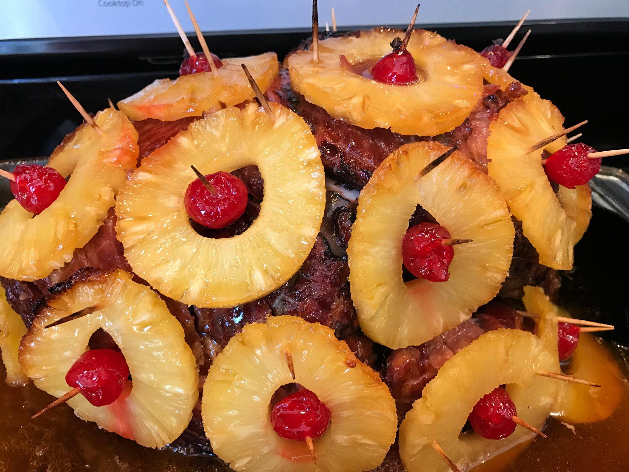 baked ham studded with pineapple rings and maraschino cherries