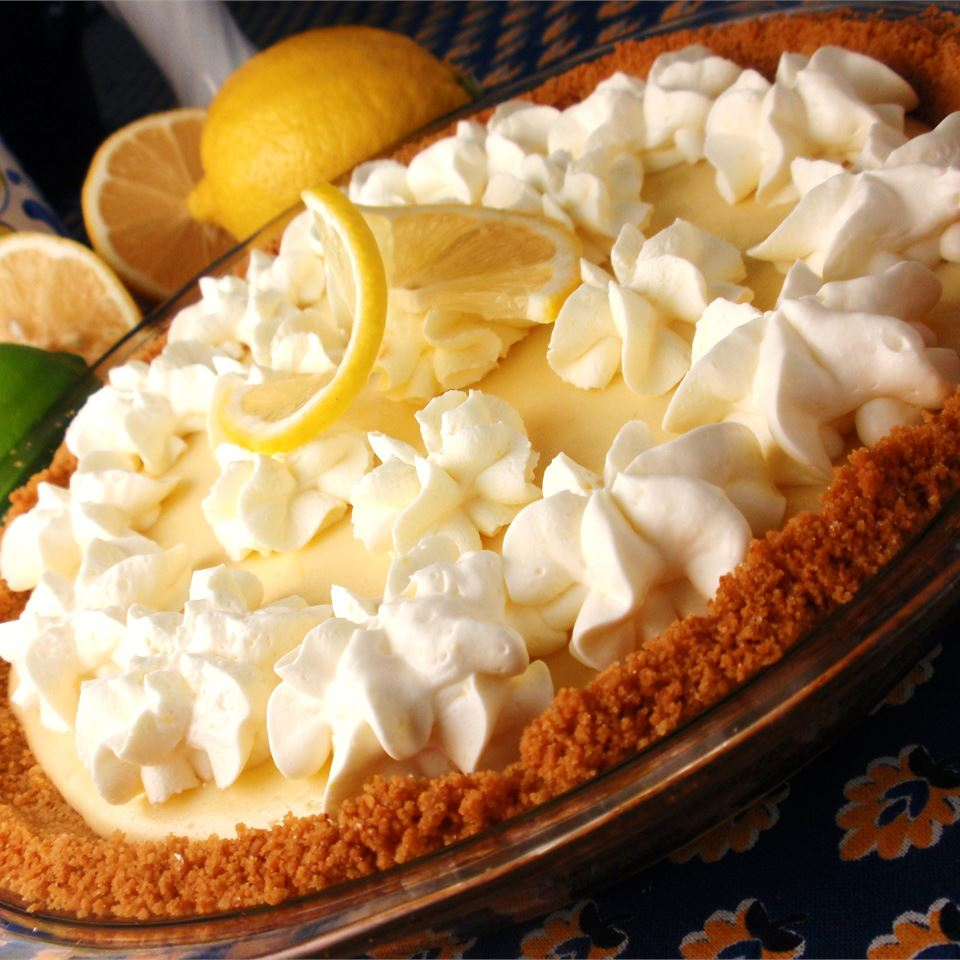 glass dish of lemon pie topped with whipped cream decoration