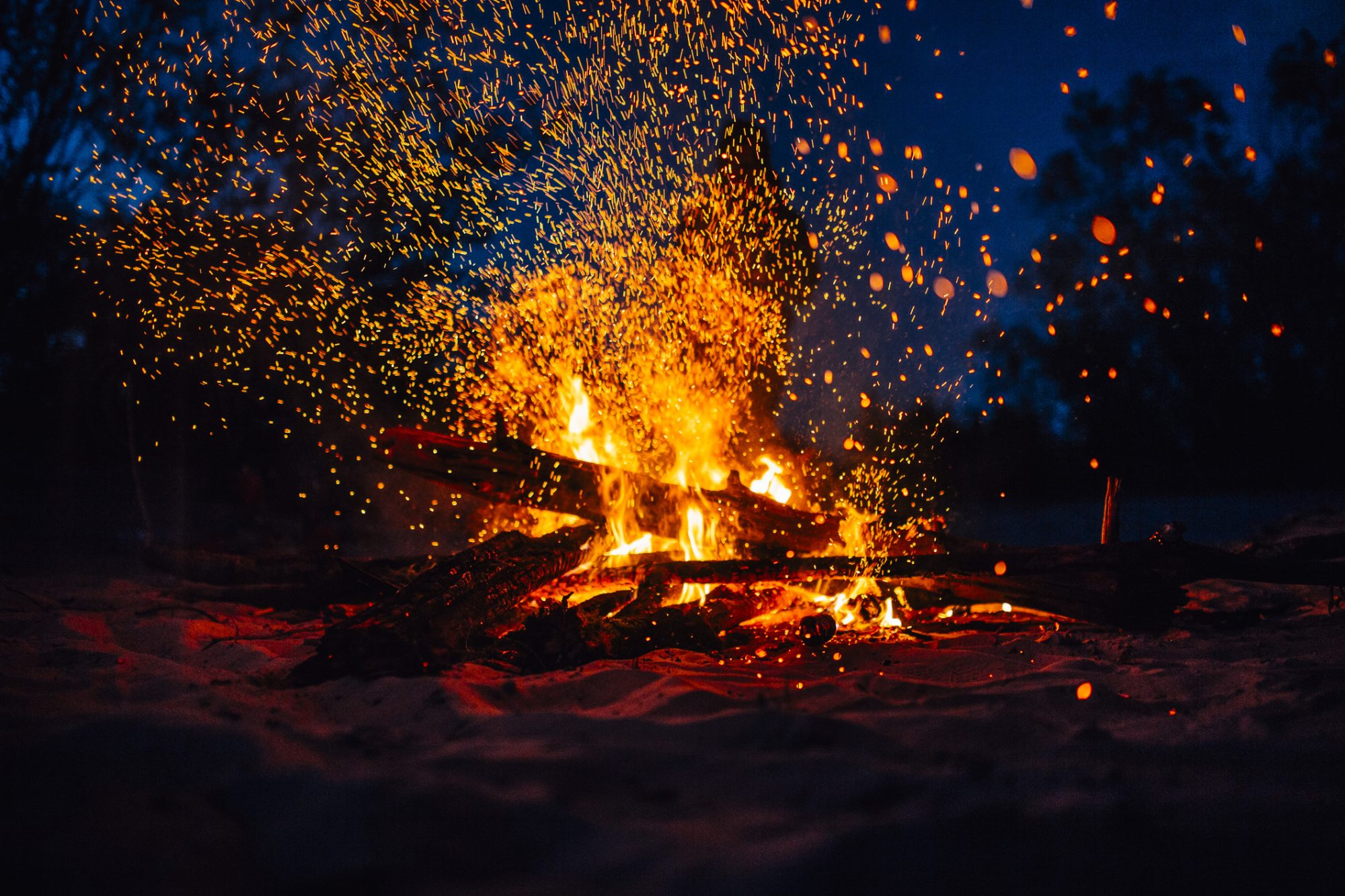 Summer beach bonfire with sparks flying around