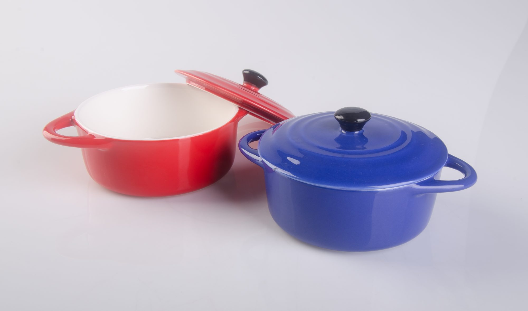 one red dutch oven and one blue dutch oven