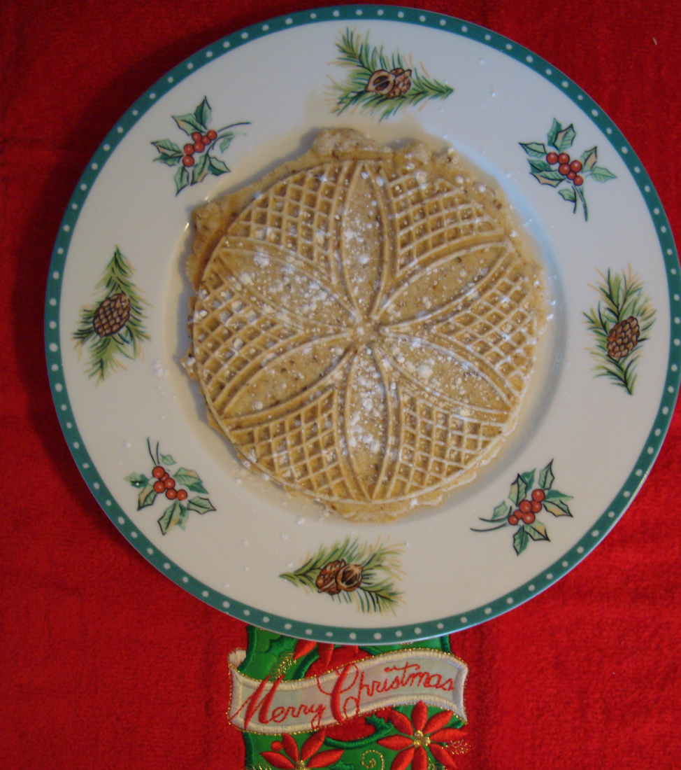 pizzelle with powdered sugar on holiday plate