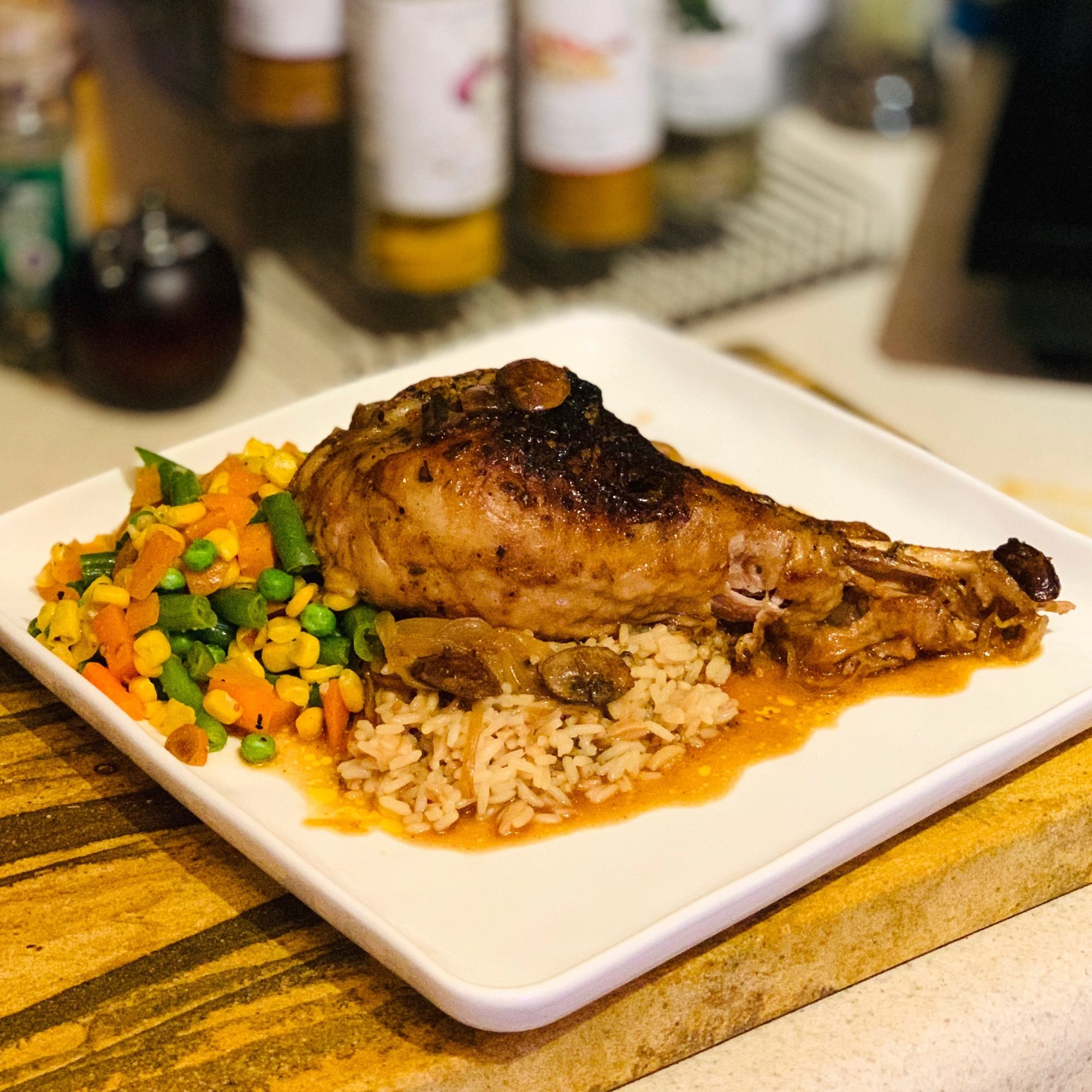 turkey leg on a plate with rice and mixed veggies