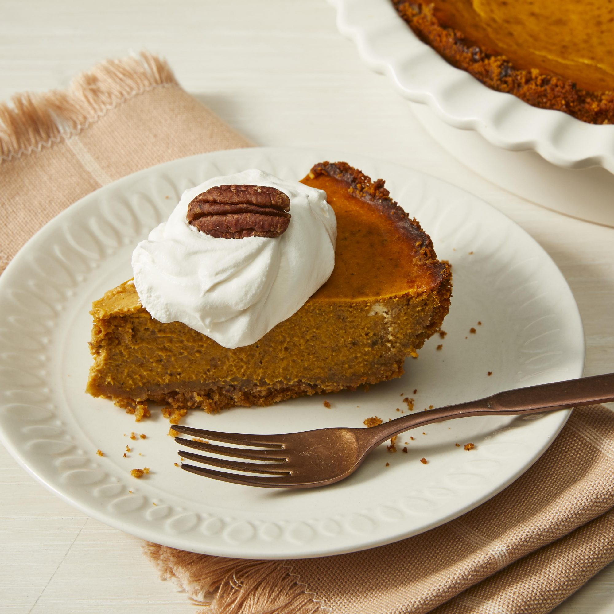 Slice of pumpkin pie with whipped cream and a pecan on top