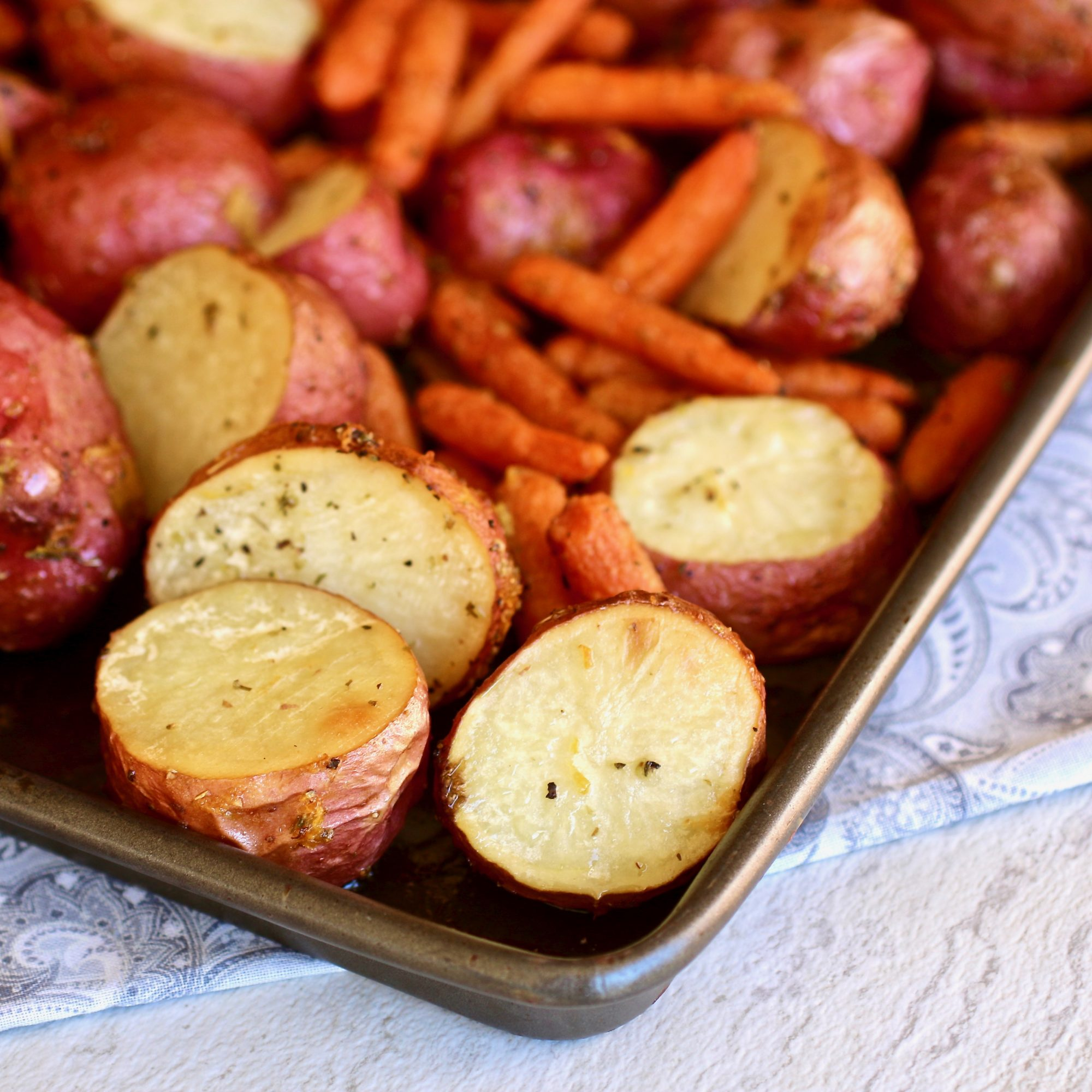 roasted baby carrots and red potatoes on a sheet pan