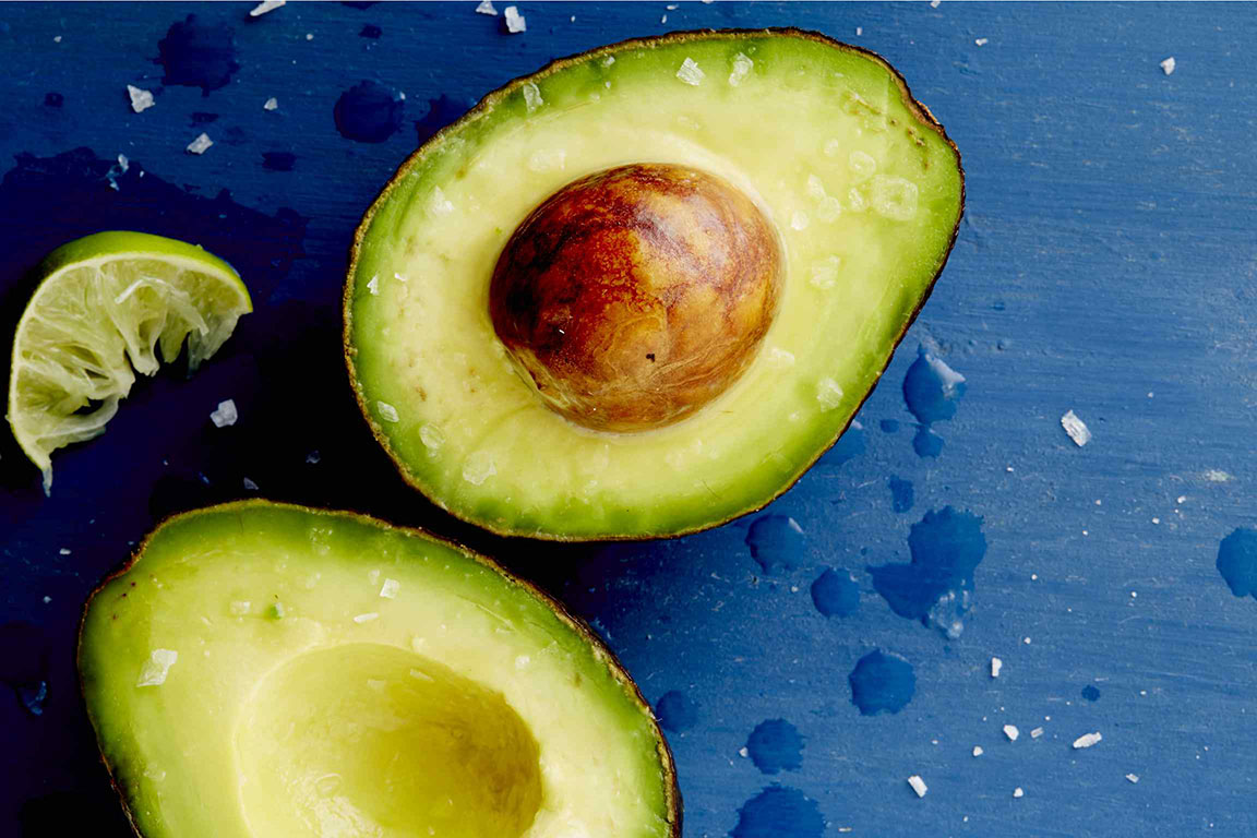 Avocado halves on blue background with lime wedge and sea salt