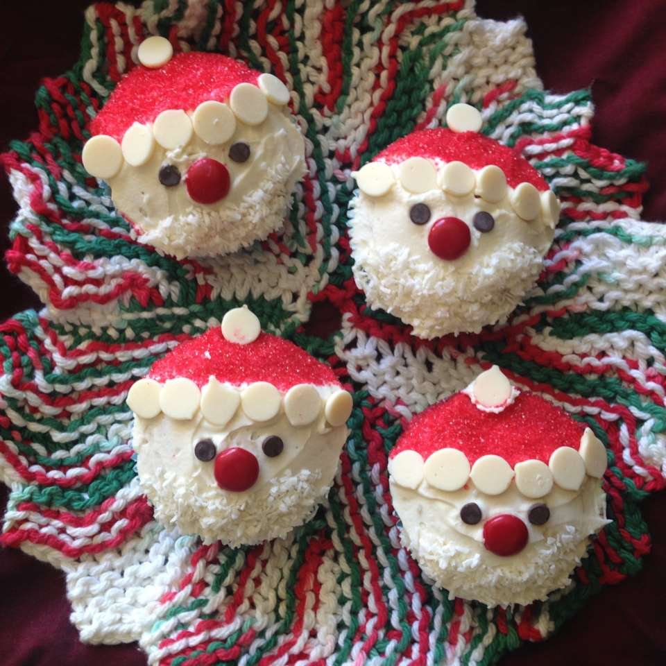 frosted vanilla cupcakes with red sprinkles and circular candy flats made to resemble Santa Claus