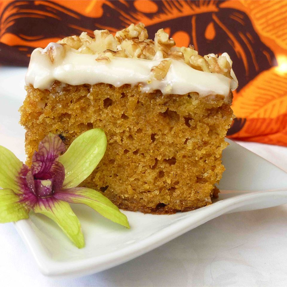 slice of pumpkin sheet cake on aw hite plate with a flower garnish