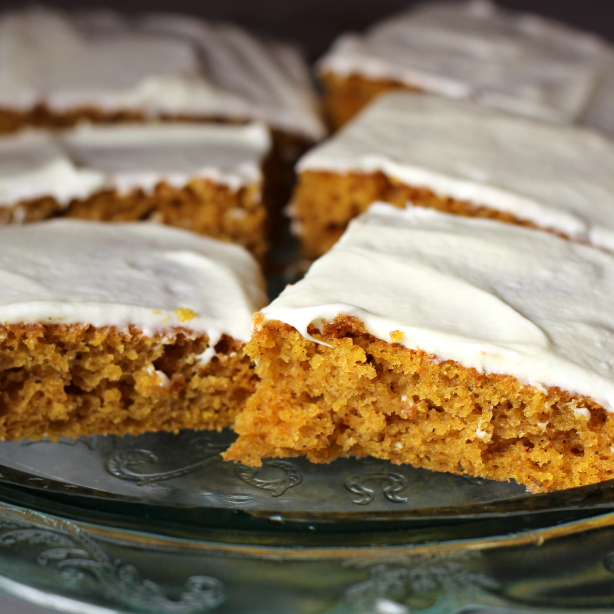 pumpkin bars with icing on a glass stand