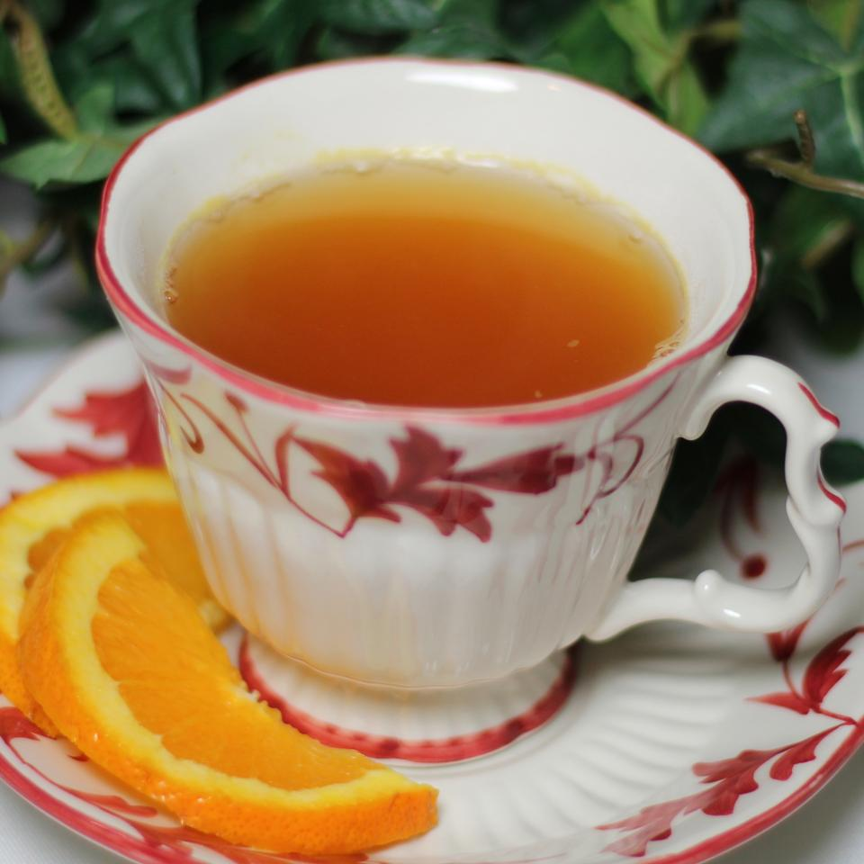 Cup of tea on china plate with orange slices