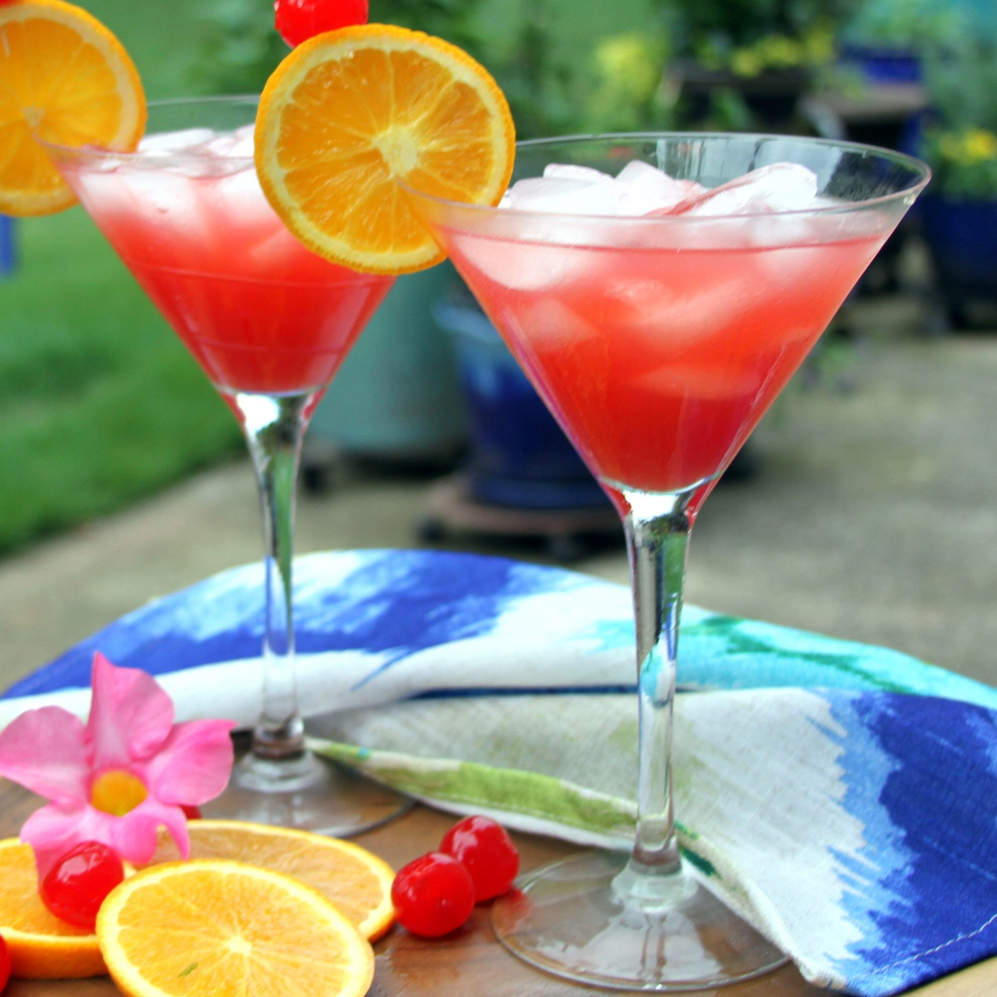 Two martini glasses with cranberry punch and orange slice garnishes