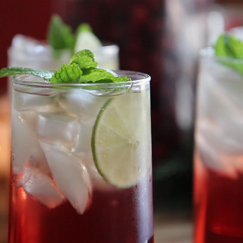 Iced cranberry punch with mint and lime wedge