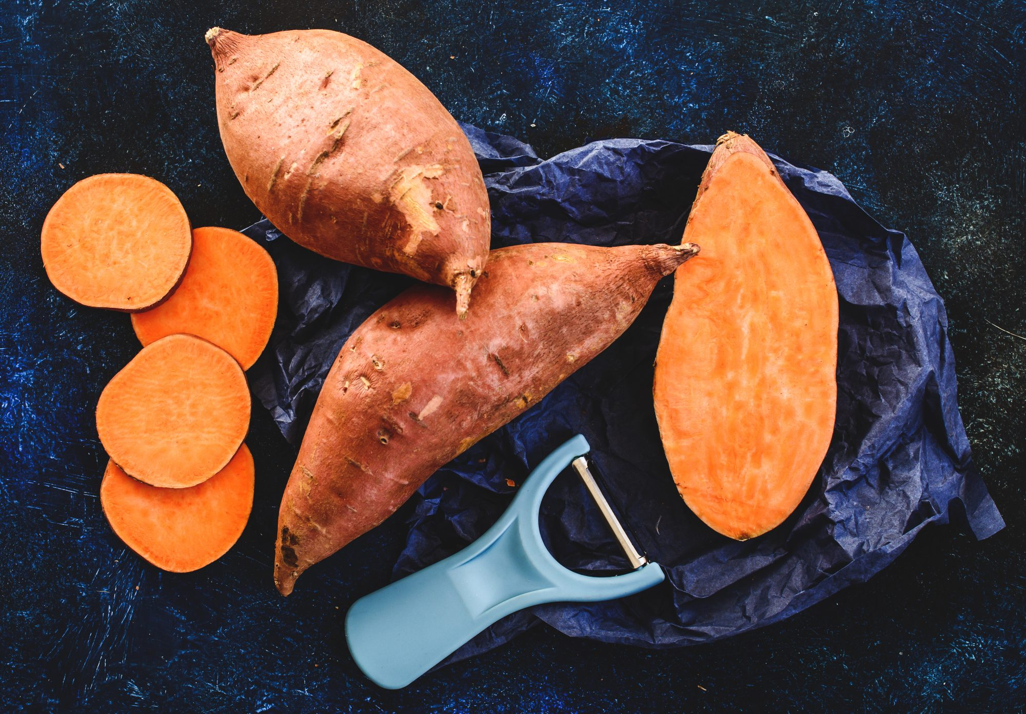whole, halved, and sliced sweet potatoes with a peeler
