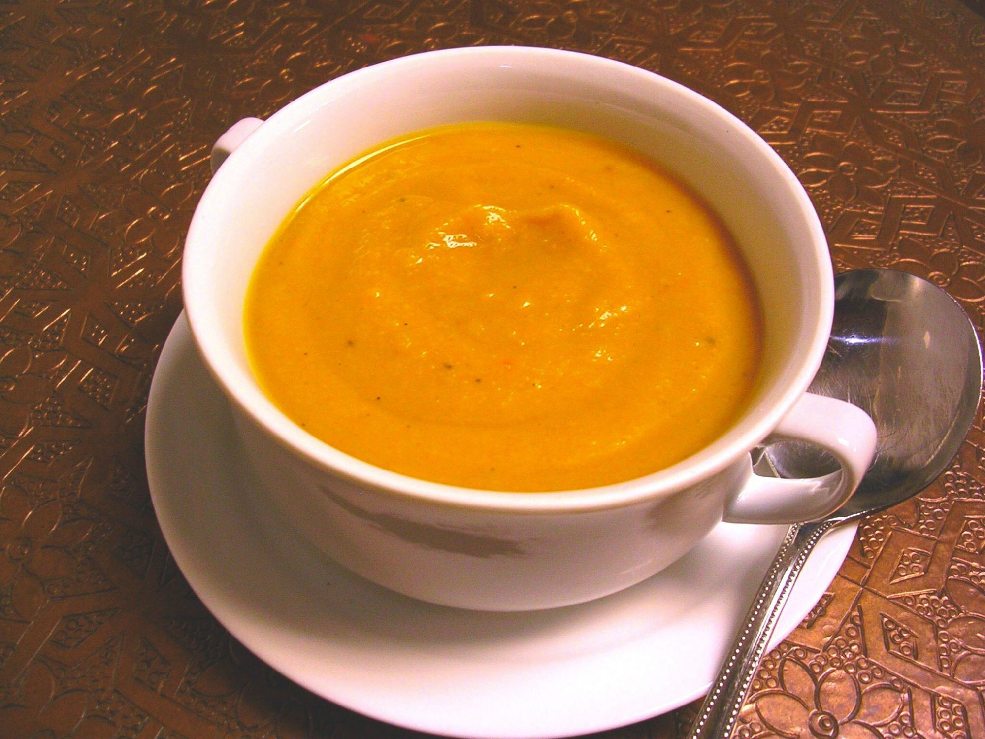 orange colored soup in in white double handed bowl on white saucer