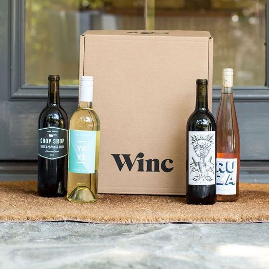 four wine bottles and a Winc subscription box