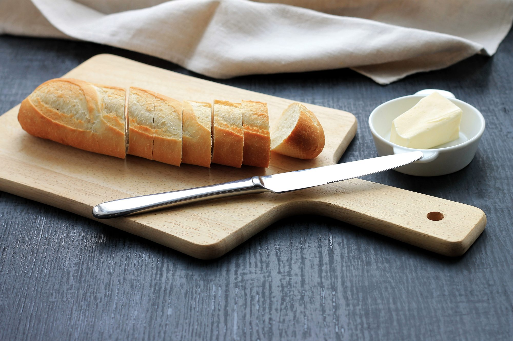 Bread (sliced baguette) on cutting board with butter on plate on dark background.