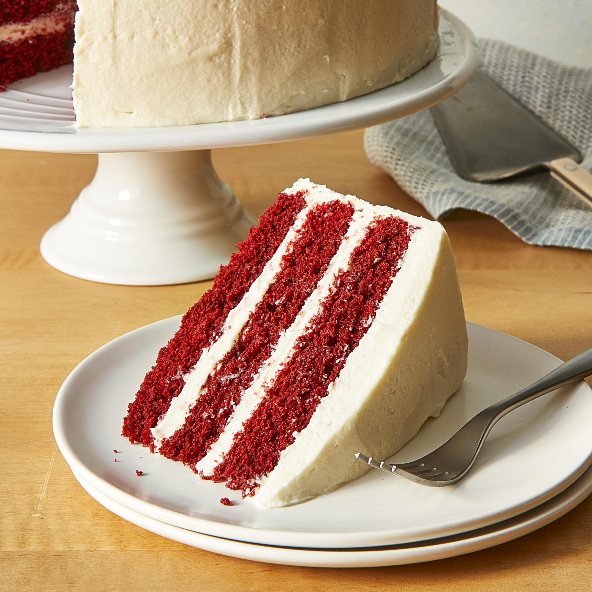 Slice of red velvet cake with the remaining cake on a stand in the background.