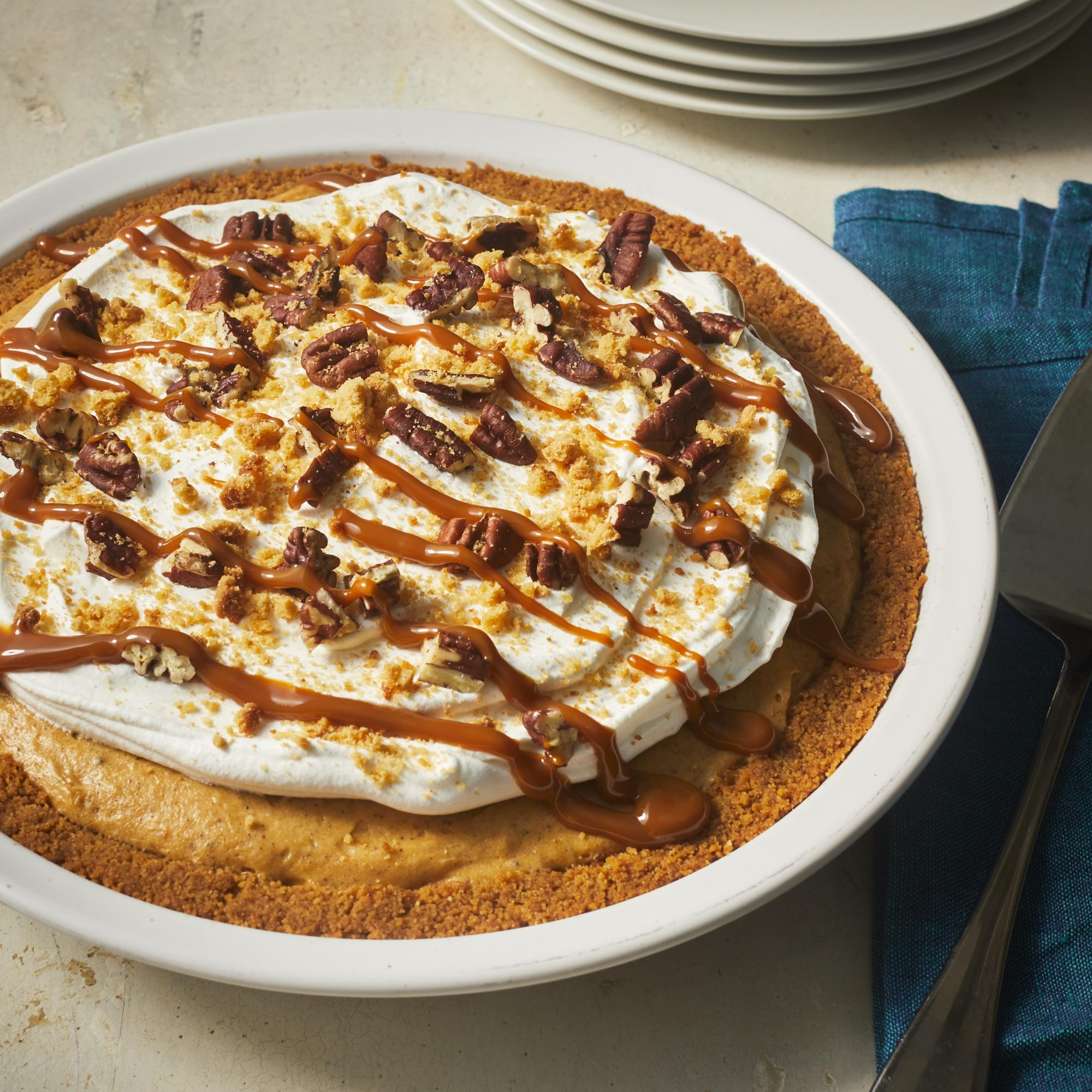 Whole pumpkin pie with whipped cream, nuts, and caramel on top.
