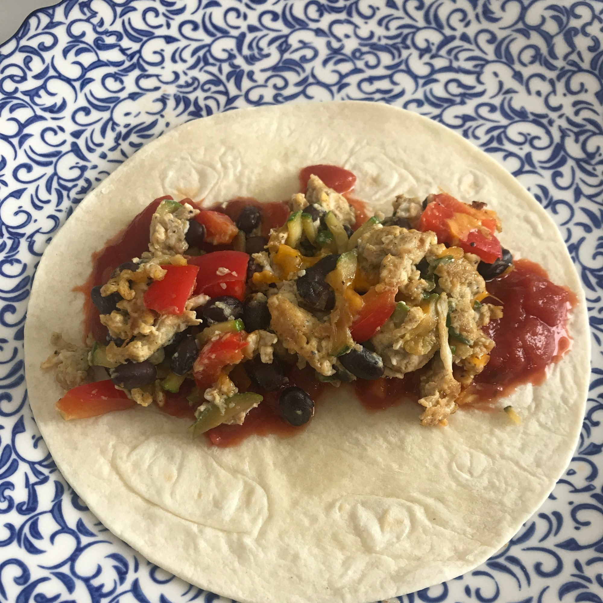 breakfast burrito splayed open on white and blue print plate